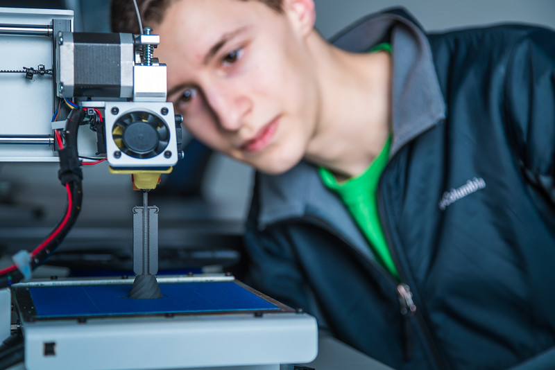 """Isaiah Ramirez keeps watch as his design project goes from concept to reality in UAF's Community and Technical College's 3-D print lab in downtown Fairbanks.  <div class=""""ss-paypal-button"""">Filename: AAR-16-4857-076.jpg</div><div class=""""ss-paypal-button-end""""></div>"""
