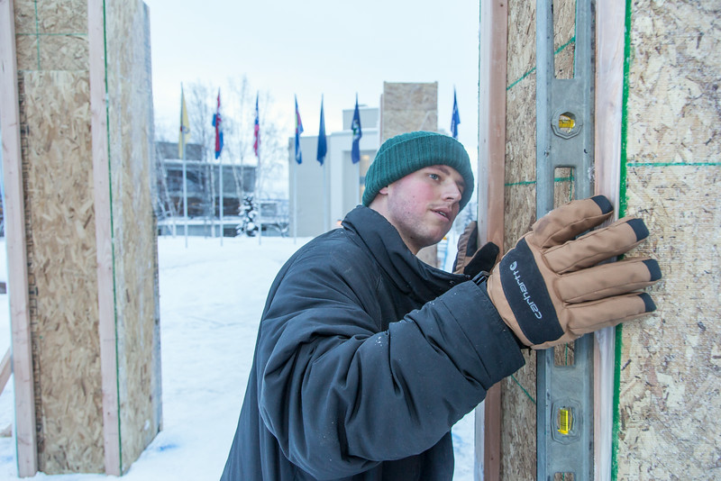 """Engineering major Tripp Collier levels one of the forms used to hold the dome during initial contruction of the 2014 ice arch, a tradition on the UAF campus for more than 50 years.  <div class=""""ss-paypal-button"""">Filename: AAR-14-4031-20.jpg</div><div class=""""ss-paypal-button-end""""></div>"""