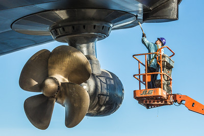 An employee at the Marinette Marine Corporation puts a final coat of paint near the rear propeller system the day before the launch of the R/V Sikuliaq Oct. 12.  Filename: AAR-12-3592-50.jpg