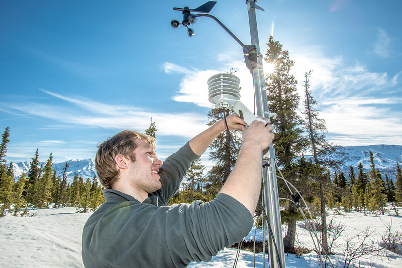 """Luke George, a senior mechanical engineering major and intern for the Alaska Center for Energy and Power, helps set up a remote meteorological station on a hillside near the Black Rapids Lodge, about 150 miles southeast of Fairbanks. The station will record wind speed and direction, as well as temperatures at different altitudes.  <div class=""""ss-paypal-button"""">Filename: AAR-13-3843-185.jpg</div><div class=""""ss-paypal-button-end"""" style=""""""""></div>"""