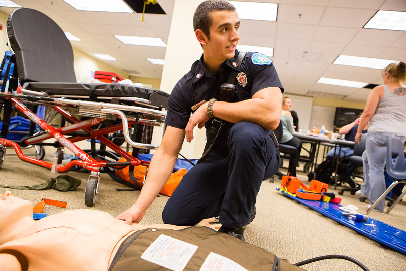 """EMT Student Michael Bellia checks the pulse of a medical training dummy while demonstrating a technique in front of his instructor.  <div class=""""ss-paypal-button"""">Filename: AAR-12-3444-2.jpg</div><div class=""""ss-paypal-button-end"""" style=""""""""></div>"""