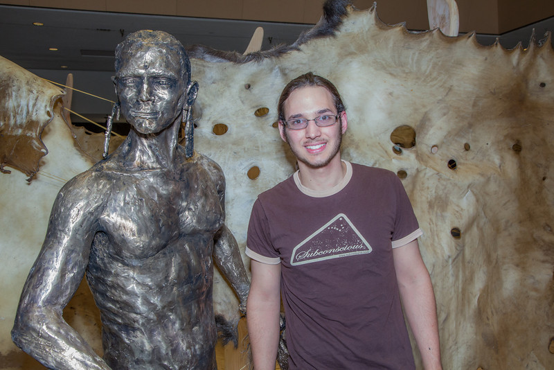 """Senior art major Joel Isaak stands next to life-sized bronze sculpture he made as part of his senior thesis project during its display in the Great Hall.  <div class=""""ss-paypal-button"""">Filename: AAR-12-3362-10.jpg</div><div class=""""ss-paypal-button-end"""" style=""""""""></div>"""