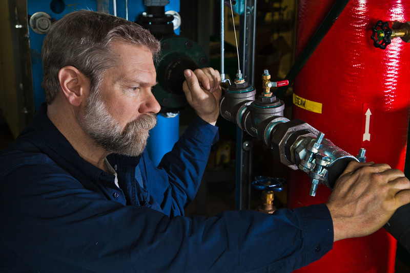 """Research professional Dave Light inspects tubing installed at the UAF Power Plant designed to help capture waste heat.  <div class=""""ss-paypal-button"""">Filename: AAR-11-3245-270.jpg</div><div class=""""ss-paypal-button-end"""" style=""""""""></div>"""