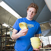 "Art major Ian Wilkinson inspects some of the 1,000-plus same-sized bowls he made for his senior thesis as he removes them from a kiln in the UAF ceramics studio.  <div class=""ss-paypal-button"">Filename: AAR-13-3744-7.jpg</div><div class=""ss-paypal-button-end"" style=""""></div>"