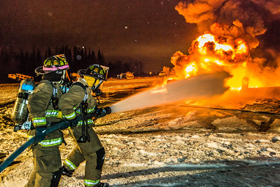 Student firefighters with the University Fire Department spray water on a blaze of burning fuel during a live training drill at the Fairbanks International Airport.  Filename: AAR-13-3995-210.jpg