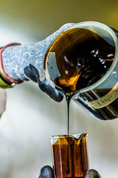 """Graduate student Mukul Chavan pours a sample of heavy crude oil from the Kaparuk field on Alaska's North Slope. Chavan and other students in UAF's petroleum engineering program are using the samples to experiment with ways to recover more oil from existing fields.  <div class=""""ss-paypal-button"""">Filename: AAR-13-3918-134.jpg</div><div class=""""ss-paypal-button-end"""" style=""""""""></div>"""