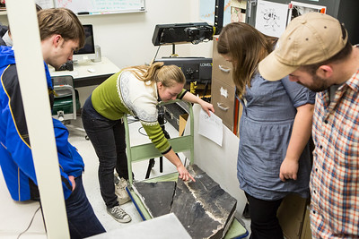 Collection Specialist Julie Rousseau presents a replica of a fossilized ichthyosaur during to a group of students during a tour of the Museum of the North's lower level during the Life in the Age of Dinosaurs lab.  Filename: AAR-14-4066-42.jpg