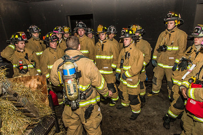 UFD Captain Ben Fleagle describes the scenario with a group of student firefighters before a live training drill at the Fairbanks Fire Training Center.  Filename: AAR-13-3978-9.jpg