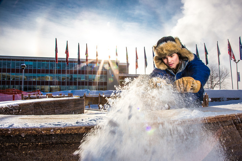 """Engineering major Ryan Williams-Cudo, project leader of the traditional ice arch project, brushes the previous night's snowfall off the main structure. Cudo and other student engineers designed and built the 2013 ice arch using a combination of water and sawdust to end up with a substance many times stronger than concrete.  <div class=""""ss-paypal-button"""">Filename: AAR-13-3733-29.jpg</div><div class=""""ss-paypal-button-end"""" style=""""""""></div>"""