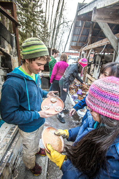 """UAF ceramic students inspect their projects after unloading them from an outdoor kiln fired with recycled vegetable oil.  <div class=""""ss-paypal-button"""">Filename: AAR-13-3814-53.jpg</div><div class=""""ss-paypal-button-end"""" style=""""""""></div>"""
