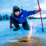 Research Associate Professor Katey Walter Anthony inspects flaming methane gas seeping from a hole in the ice on the surface of a pond on the UAF campus. The naturally occurring phenomenon i ...