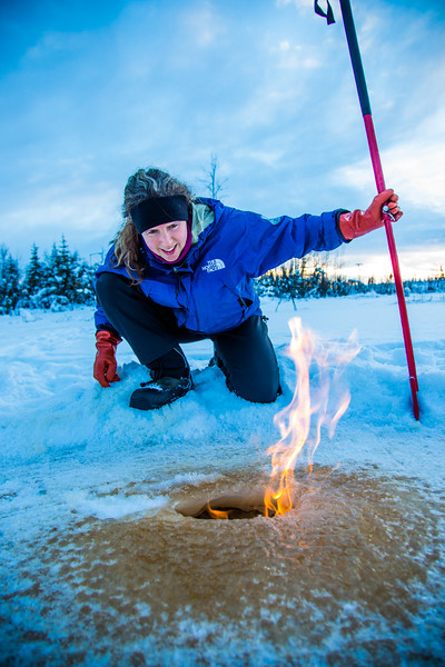 """Research Associate Professor Katey Walter Anthony inspects flaming methane gas seeping from a hole in the ice on the surface of a pond on the UAF campus. The naturally occurring phenomenon is made worse by thawing permafrost and increased plant decay caused by global warming.  <div class=""""ss-paypal-button"""">Filename: AAR-16-4815-24.jpg</div><div class=""""ss-paypal-button-end""""></div>"""