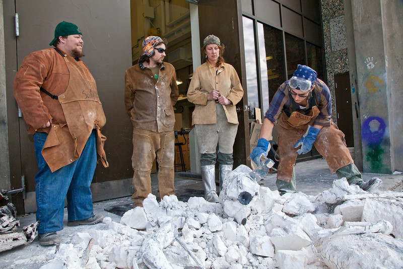 """Art major Joel Isaak, rights chips off the rubble of the plaster cast covering pieces of cooling bronze he'll use to build a life-sized sculpture for his senior thesis.  <div class=""""ss-paypal-button"""">Filename: AAR-12-3341-14.jpg</div><div class=""""ss-paypal-button-end"""" style=""""""""></div>"""
