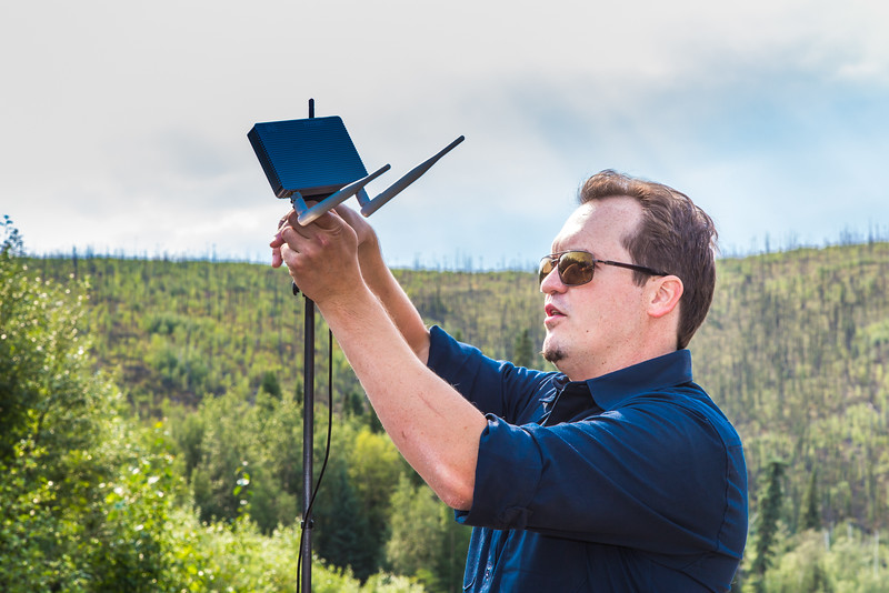 """Trevor Parcell with the Alaska Center for Unmanned Aircraft Systems Integration (ACUASI) sets up a piloting station on a gravel bar along the upper Chena River. The UAV pilot was taking part in a joint effort with the U.S. Fish and Wildlife Service to collect video of important king salmon spawning habitat.  <div class=""""ss-paypal-button"""">Filename: AAR-15-4593-109.jpg</div><div class=""""ss-paypal-button-end""""></div>"""