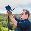 "Trevor Parcell with the Alaska Center for Unmanned Aircraft Systems Integration (ACUASI) sets up a piloting station on a gravel bar along the upper Chena River. The UAV pilot was taking part in a joint effort with the U.S. Fish and Wildlife Service to collect video of important king salmon spawning habitat.  <div class=""ss-paypal-button"">Filename: AAR-15-4593-109.jpg</div><div class=""ss-paypal-button-end""></div>"