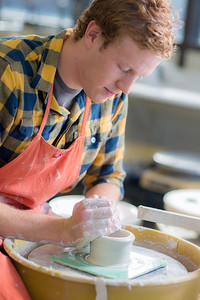 Art major Ian Wilkinson works on one of approximately 1,000 ceramic bowls needed for his senior thesis project in the fine arts complex on the Fairbanks campus.  Filename: AAR-12-3547-049.jpg