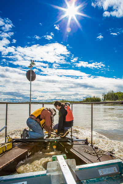 "Jack Schmid, left, and Paul Duvoy, research professionals with the Alaska Center for Energy and Power, take measurements on a prototype deployment boom on the Tanana River near Nenana. The pair are part of a team conducting research on the feasibility of using the river current to generate electricity for potential use throughout rural Alaska.  <div class=""ss-paypal-button"">Filename: AAR-12-3500-059.jpg</div><div class=""ss-paypal-button-end"" style=""""></div>"