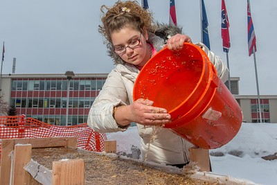 Civil engineering major Katrina Monta adds water to a mixture combined with sawdust which when frozen, hardens into a substance many times stronger than concrete. Katrina and others are hard at work on this year's traditional ice arch, designed and built each year by engineering students.  Filename: AAR-13-3727-28.jpg