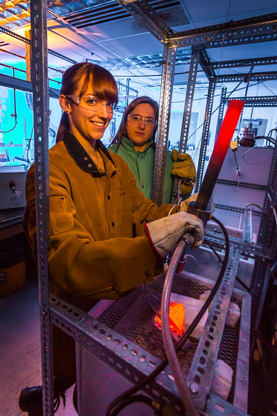 "Ph.D. candidate Amanda Lindoo pulls a rod containing volcanic remnants from a furnace in the Reichardt Building petrology lab under the watchful gaze of Research Assistant Professor Jessica Larsen.  <div class=""ss-paypal-button"">Filename: AAR-16-4828-061.jpg</div><div class=""ss-paypal-button-end""></div>"