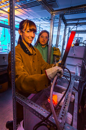 Ph.D. candidate Amanda Lindoo pulls a rod containing volcanic remnants from a furnace in the Reichardt Building petrology lab under the watchful gaze of Research Assistant Professor Jessica Larsen.  Filename: AAR-16-4828-061.jpg
