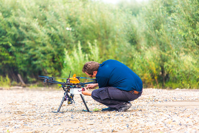 Trevor Parcell with the Alaska Center for Unmanned Aircraft Systems Integration (ACUASI) adjusts an unmanned aerial vehicle used to collect video of a popular stretch of the upper Chena River which serves as prime king salmon habitat.  Filename: AAR-15-4593-285.jpg
