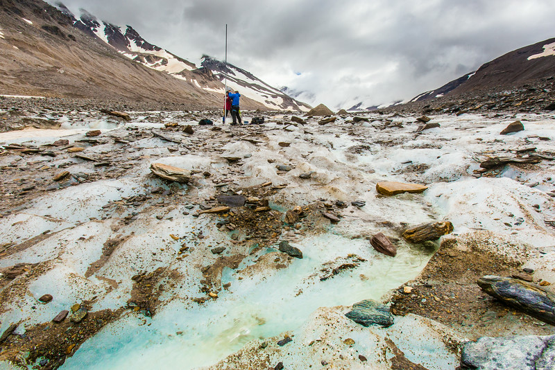 """Professor Regine Hock, a glaciologist with UAF's Geophysical Institute, and Tristan Weiss, a research technician with the Institute of Northern Engineering, measure the depth of the ice near the toe of the Jarvis Glacier in the eastern Alaska Range.  <div class=""""ss-paypal-button"""">Filename: AAR-14-4256-447.jpg</div><div class=""""ss-paypal-button-end""""></div>"""