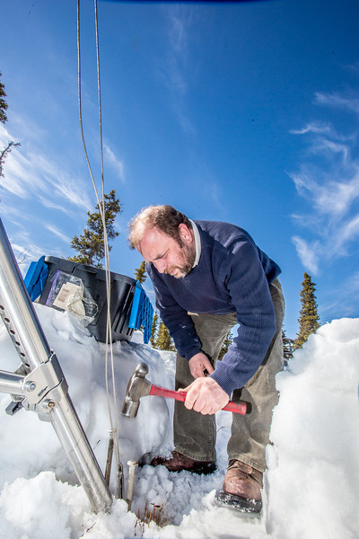 "Research associate professor Javier Fochesatto, helps set up a remote meteorological station on a hillside near the Black Rapids Lodge, about 150 miles southeast of Fairbanks. The station will record wind speed and direction, as well as temperatures at different altitudes.  <div class=""ss-paypal-button"">Filename: AAR-13-3843-101.jpg</div><div class=""ss-paypal-button-end"" style=""""></div>"