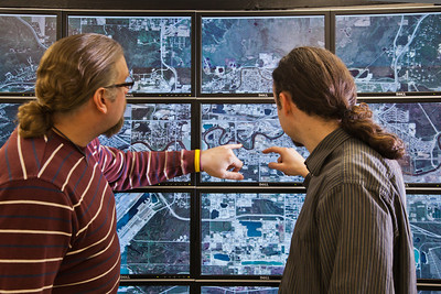 Computer science faculty members Jon Genetti, left, and Orion Lawlor inspect a high resolution aerial photo of Fairbanks on the bioinformatics powerwall in the Chapman Building.  Filename: AAR-12-3272-148.jpg
