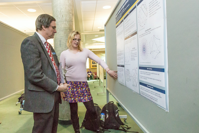 """Paul Layer, dean of UAF's College of Natural Science and Mathematics Dean, listens to a student presentation during UAF's Research Day Poster Session in Wood Center.  <div class=""""ss-paypal-button"""">Filename: AAR-14-4169-28.jpg</div><div class=""""ss-paypal-button-end""""></div>"""