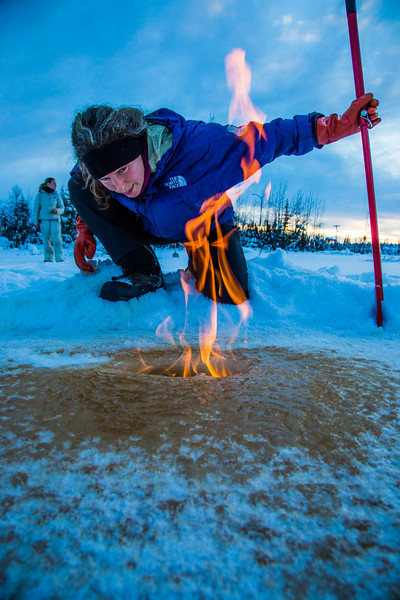 """Research Associate Professor Katey Walter Anthony inspects flaming methane gas seeping from a hole in the ice on the surface of a pond on the UAF campus. The naturally occurring phenomenon is made worse by thawing permafrost and increased plant decay caused by global warming.  <div class=""""ss-paypal-button"""">Filename: AAR-16-4815-21.jpg</div><div class=""""ss-paypal-button-end""""></div>"""