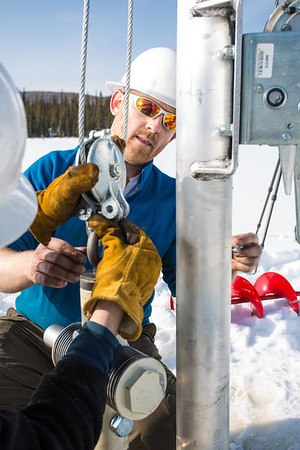 Associate Professor Mat Wooller tests a new vibra-coring system through a hole in lake ice to sample long cores of sediment deep below the lake's bottom.  Filename: AAR-12-3346-033.jpg