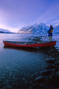 Peter Mather perched beside his Red Mad River Canoe on Kathleen Lake in Kluane National Park. A winter scene with snow covered St. Elias Mountains in the background.