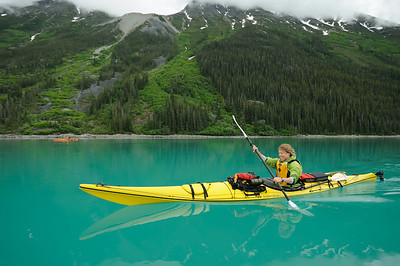 Stephanie Ryan solo Kayaking in the deep green waters of glacial fed Tagish Lake, part of the Southern Lake region of the Yukon and Northern British Columbia, headwaters of the Yukon River. Deep green forest and waterfall creek in the background. Canada