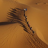 Dune riders after sunrise in the Sahara, Morocco.