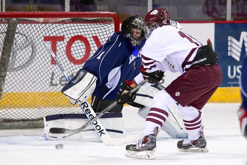 Cheyenne Mountain senior Nick Garland (18) takes a shot against Air Academy junior Cole Chiga (1) in the first period. The Air Academy Kadets defeated the Cheyenne Mountain Indians 4-2 in boys' hockey action on Tuesday, December 5, 2014 at The Broadmoor World Arena. Photo by Isaiah J. Downing