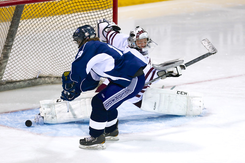 Cheyenne Mountain sophomore Ryan McCann (31) makes a save against Air Academy senior Jonathan Valtin (19) in the second period. The Air Academy Kadets defeated the Cheyenne Mountain Indians 4-2 in boys' hockey action on Tuesday, December 5, 2014 at The Broadmoor World Arena. Photo by Isaiah J. Downing
