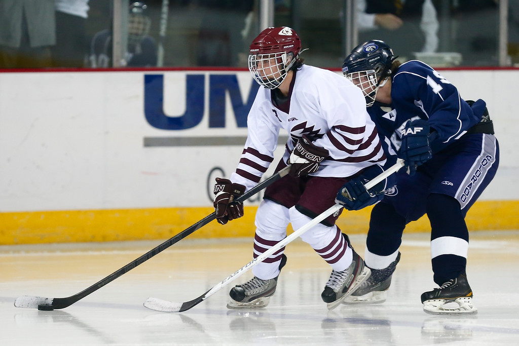 Cheyenne Mountain senior Doug Klopenstine (3) controls the puck against Air Academy senior Jonathan Valtin (19) in the third period. The Air Academy Kadets defeated the Cheyenne Mountain Indians 4-2 in boys' hockey action on Tuesday, December 5, 2014 at The Broadmoor World Arena. Photo by Isaiah J. Downing