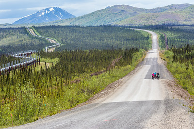 Cyclists make their way along a lonely stretch of the Dalton Highway which mostly parallels the trans-Alaska pipeline from just north of Fairbanks to Deadhorse near the Arctic Ocean.  Filename: AKA-14-4213-053.jpg