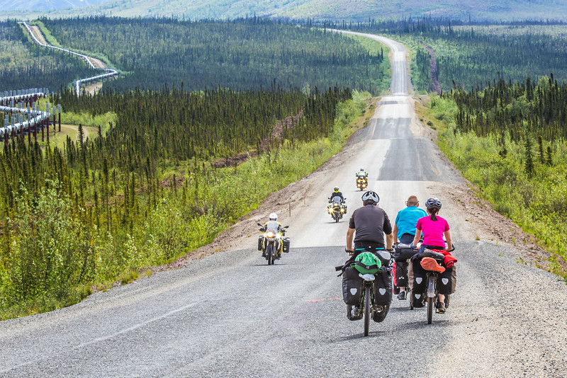 """Cyclists make their way along a lonely stretch of the Dalton Highway which mostly parallels the trans-Alaska pipeline from just north of Fairbanks to Deadhorse near the Arctic Ocean.  <div class=""""ss-paypal-button"""">Filename: AKA-14-4213-044.jpg</div><div class=""""ss-paypal-button-end""""></div>"""