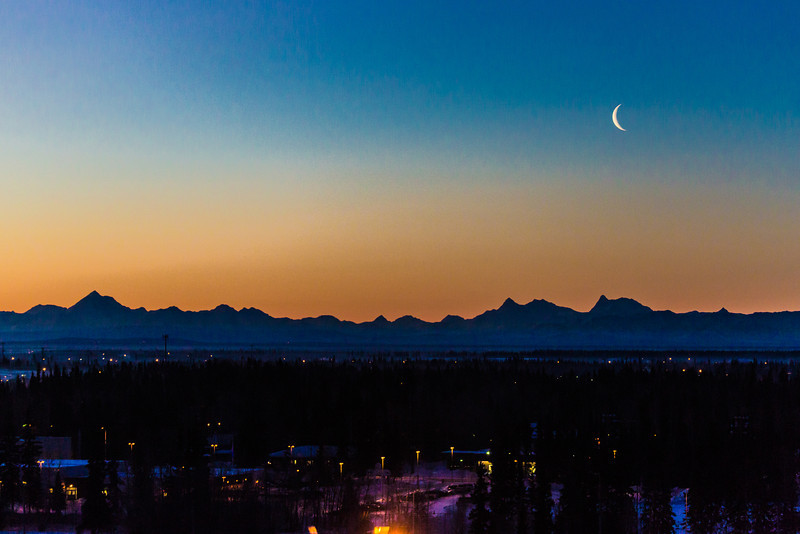 "A crescent moon shines over the Alaska Range peaks of Mt. Hayes, Hess and Deborah on a January morning from the UAF campus in Fairbanks.  <div class=""ss-paypal-button"">Filename: AKA-14-4048-15.jpg</div><div class=""ss-paypal-button-end"" style=""""></div>"