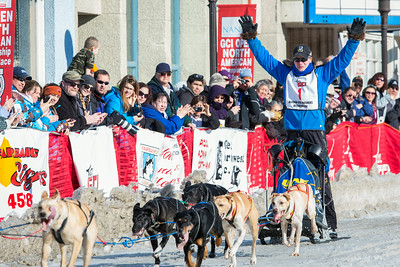 With hands in the air as he crosses the finish line Associate Professor and Associate Dean of Veterinary Medicine Arleigh Reynolds clinches the first place of the 2014 Open North American Sled Dog Race in downtown Fairbanks.  Filename: AKA-14-4120-44.jpg