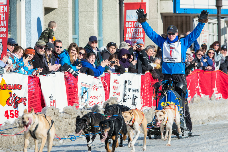 "With hands in the air as he crosses the finish line Associate Professor and Associate Dean of Veterinary Medicine Arleigh Reynolds clinches the first place of the 2014 Open North American Sled Dog Race in downtown Fairbanks.  <div class=""ss-paypal-button"">Filename: AKA-14-4120-44.jpg</div><div class=""ss-paypal-button-end""></div>"