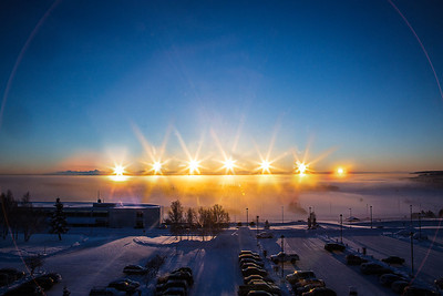 The sun rises and sets above the Alaska Range south of Fairbanks in this composite image taken from the Akasofu Building on the UAF campus on Dec. 21, the day of the winter solstice.  Filename: AKA-12-3685-comp.jpg