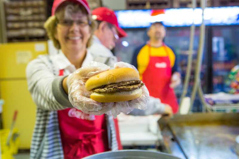 """Ann Ringstad, UAF's Community Advocacy director, serves up a tasty double during her shift at the UAF Alumni Hamburger Booth Tuesday at the Tanana Valley State Fair.  <div class=""""ss-paypal-button"""">Filename: AKA-12-3486-101.jpg</div><div class=""""ss-paypal-button-end"""" style=""""""""></div>"""