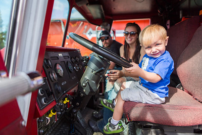 Wearing an Alaska Nanooks shirt, Trenton Reabold is all smiles at the driver's seat of a UAF Fire Department fire truck during UAF Day at the Tanana Valley State Fair.  Filename: AKA-13-3900-63.jpg