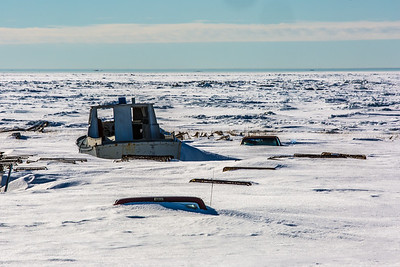 Old boats and vehicles lie under the snow along the Seward Peninsula coast near Nome, site of UAF's Northwest Campus.  Filename: AKA-16-4865-122.jpg