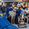 "Associate Professor and Associate Dean of Veterinary Medicine Arleigh Reynolds pauses for a portrait with his family after winning the first place of the 2014 Open North American Sled Dog Race in downtown Fairbanks.  <div class=""ss-paypal-button"">Filename: AKA-14-4120-120.jpg</div><div class=""ss-paypal-button-end""></div>"