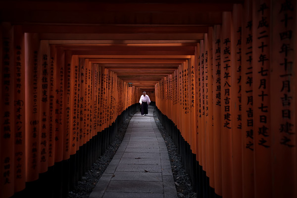 Photograph: Fushimi Inari - A man walking through the thousand torii gates of Fushimi Inari in Kyoto, Japan.