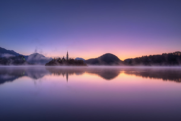 Photograph: Purple Haze - Purple and orange sunrise over Lake Bled in Slovenia.