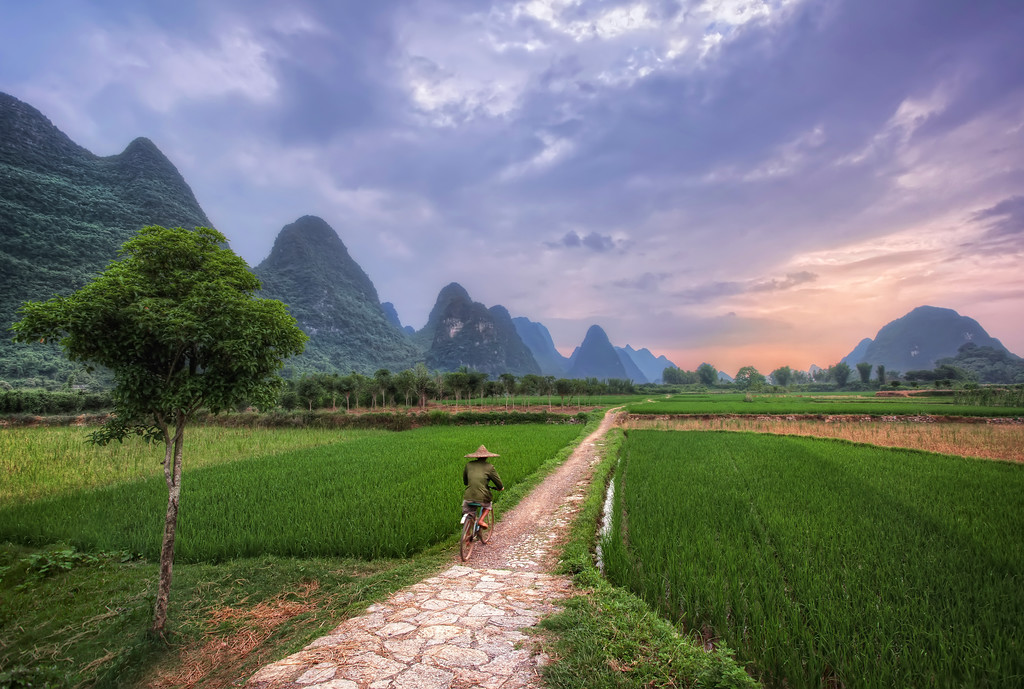 Photograph: Yangshuo Cyclist - A man in Yangshuo, Guilin, China rides his bicycle along a path toward the sun, setting behind some karst mountains.
